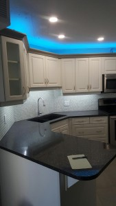 Downtown condo LED disks with LED accents above and below cabinets